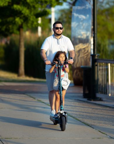 man and girl riding an electric scooter